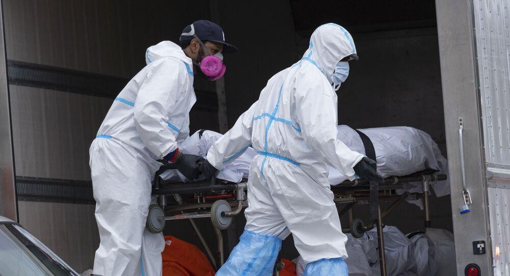 Pracownicy w kombinezonach ochronnych umieszczają ciało w lodówce w Nowym Jorku