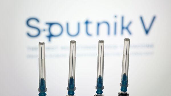 "Strzykawki na tle logo ""Sputnik V"" - Sputnik Polska"
