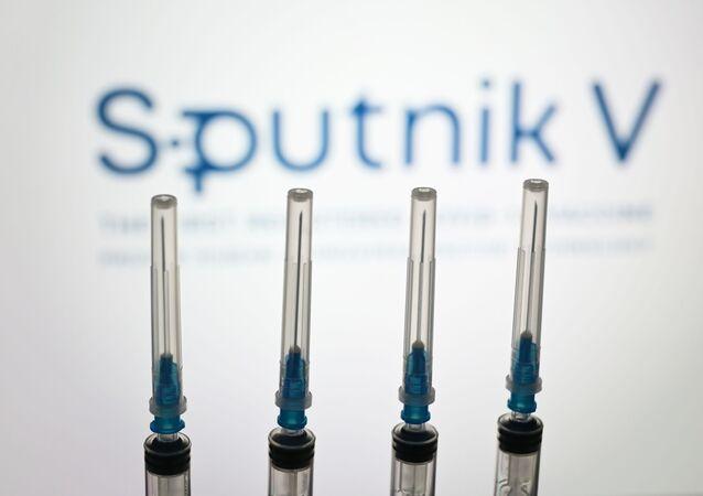 """Strzykawki na tle logo """"Sputnik V"""""""