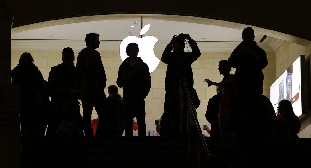 Sylwetki ludzi przed logo Apple