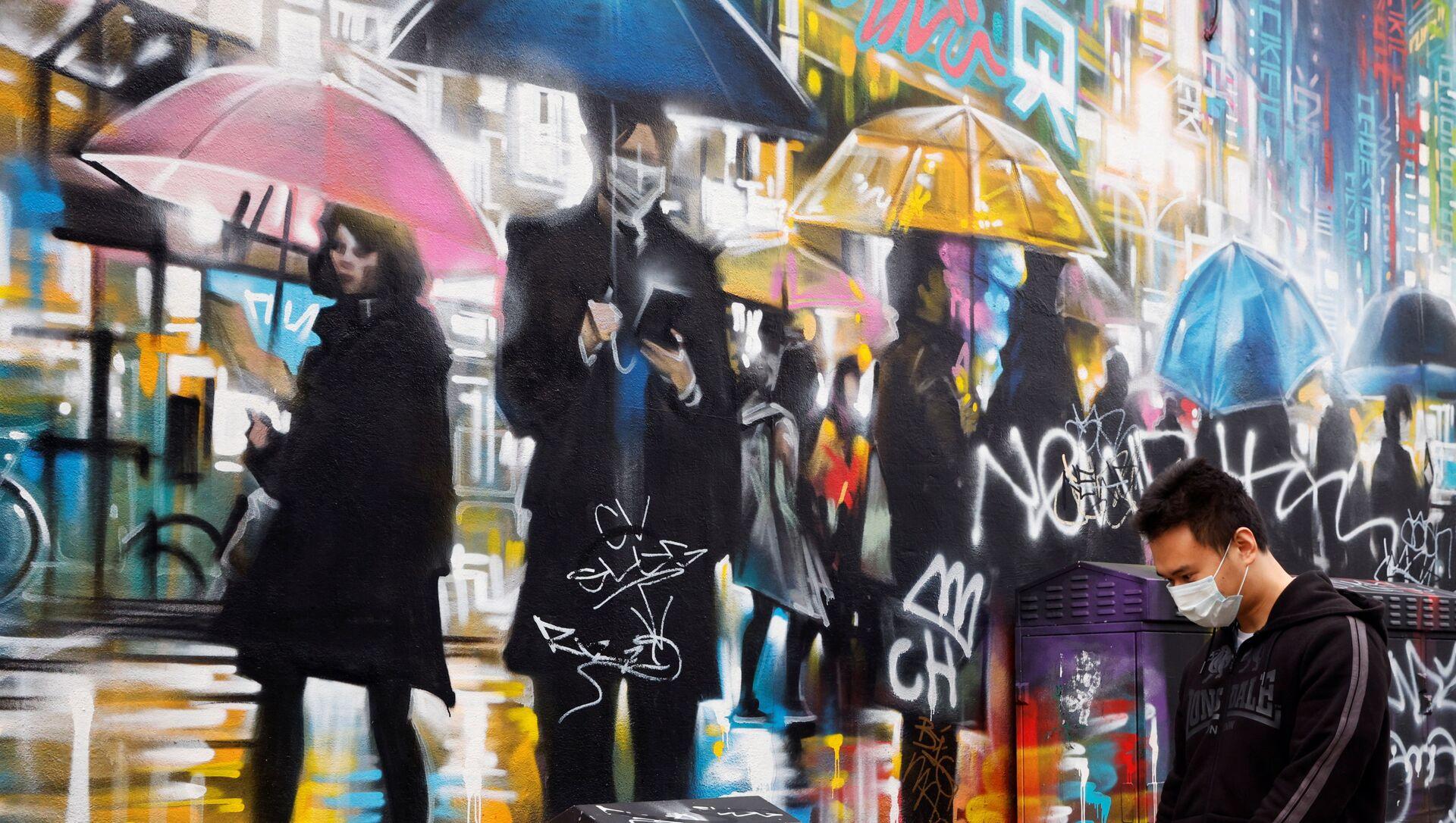 A man wearing a face mask walks past graffiti, amid the outbreak of the coronavirus disease (COVID-19) in London, Britain January 19, 2021 - Sputnik Polska, 1920, 16.02.2021