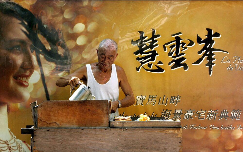 Mężczyzna podczas przygotowywania naleśników na ulicy w Hongkongu