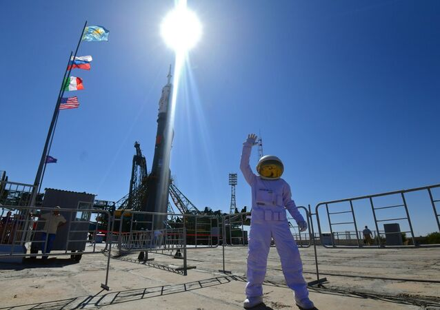 Mężczyzna w stroju astronauty sfotografowany na tle rakiety