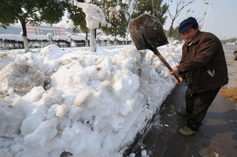 Chiński robotnik czyści ulice z obfitych opadów śniegu w Chinach, 2008 rok