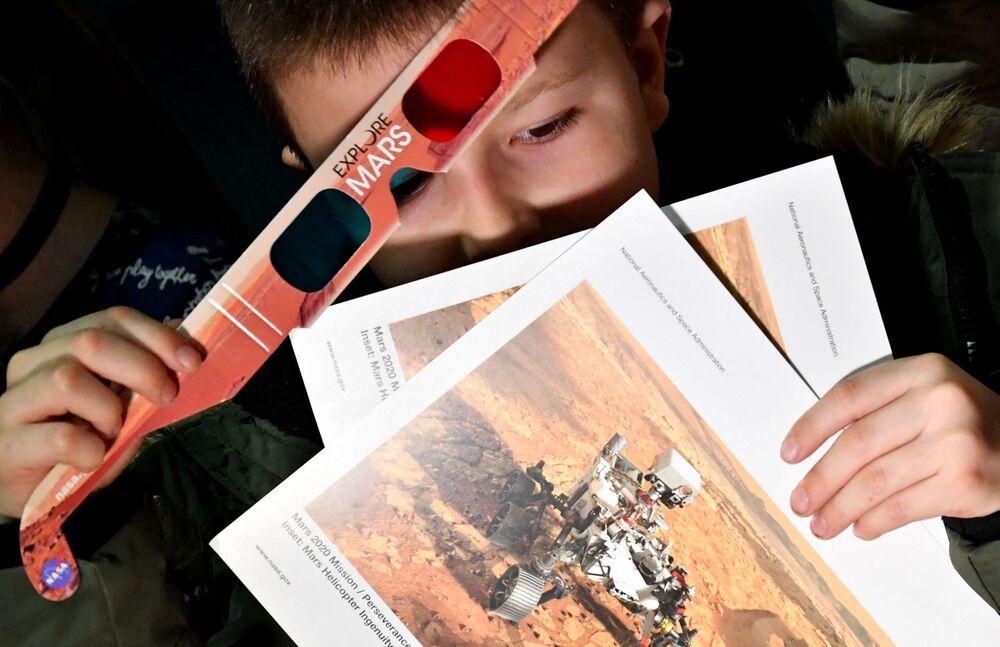 Chłopiec trzyma okulary 3D i ulotki w szkole podstawowej, świętując lądowanie łazika Marsa Perseverance NASA na Marsie