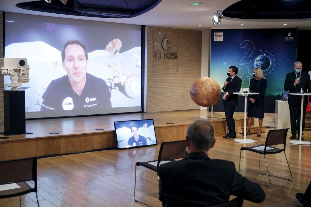 Francuski astronauta Thomas Pesce na ekranie podczas wizyty Emmanuela Macrona i jego żony w Narodowym Centrum Badań Kosmicznych w Paryżu