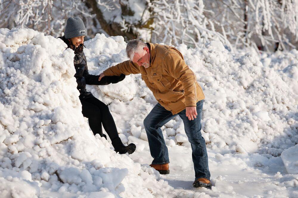 Ludzie pomagają sobie przedostać się przez ogromny śnieg w miejskim parku Niagara Falls w Nowym Jorku