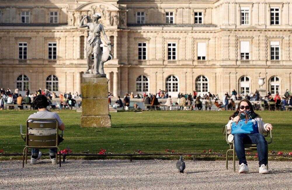 Ludzie korzystają z ciepłej pogody i odpoczywają w Ogrodzie Luksemburskim