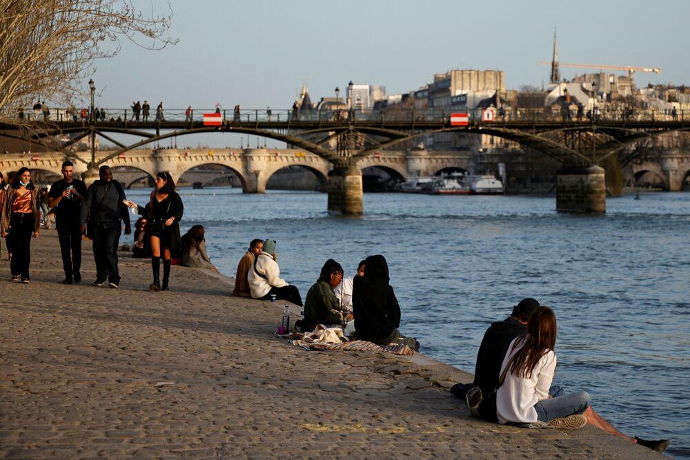 Ludzie odpoczywają nad rzeką w Paryżu