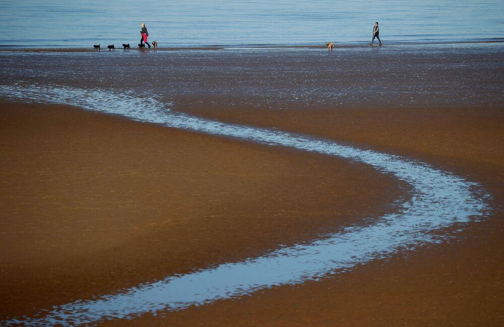 Ludzie spacerują po plaży w Wielkiej Brytanii