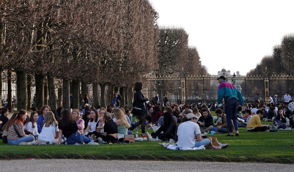 Ludzie cieszą się słoneczną pogodą i odpoczywają w Ogrodzie Luksemburskim w Paryżu