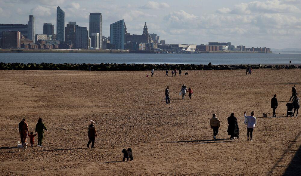 Ludzie spacerują po plaży w  New Brighton w Wielkiej Brytanii