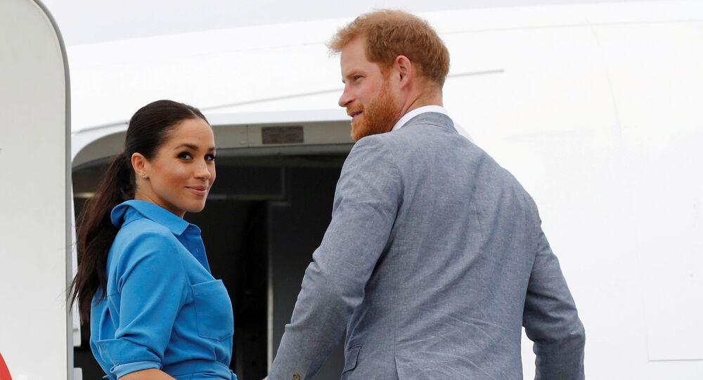 Brytyjski książę Harry i Meghan, księżna Sussex patrzą przed odlotem z międzynarodowego lotniska Fua'amotu na Tonga 26 października 2018 r.