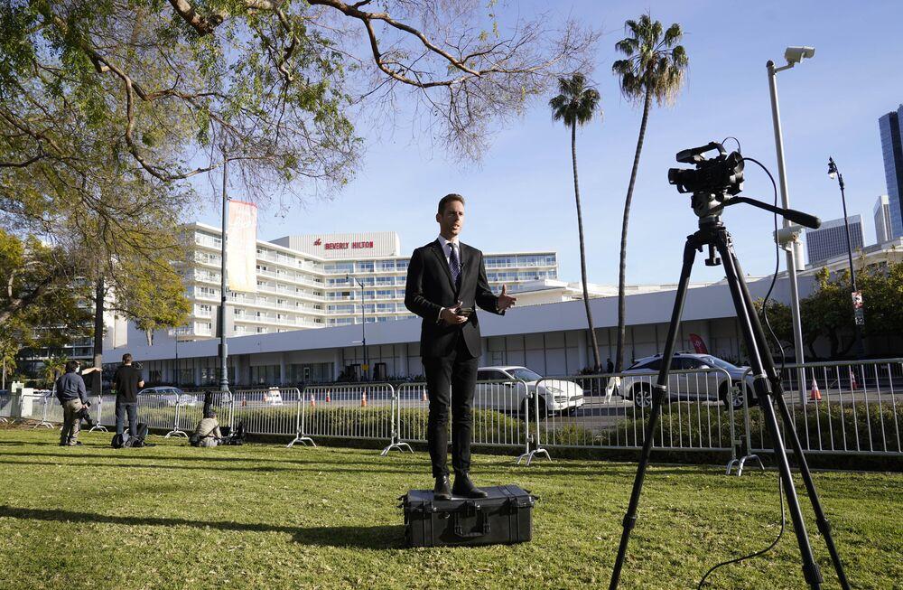 Репортер у отеля Беверли-Хилтон во время церемонии награждения премии Золотой глобус в США.