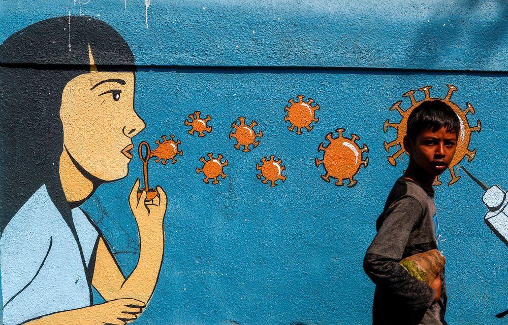 Chłopiec przechodzi obok graffiti w Bombaju w Indiach