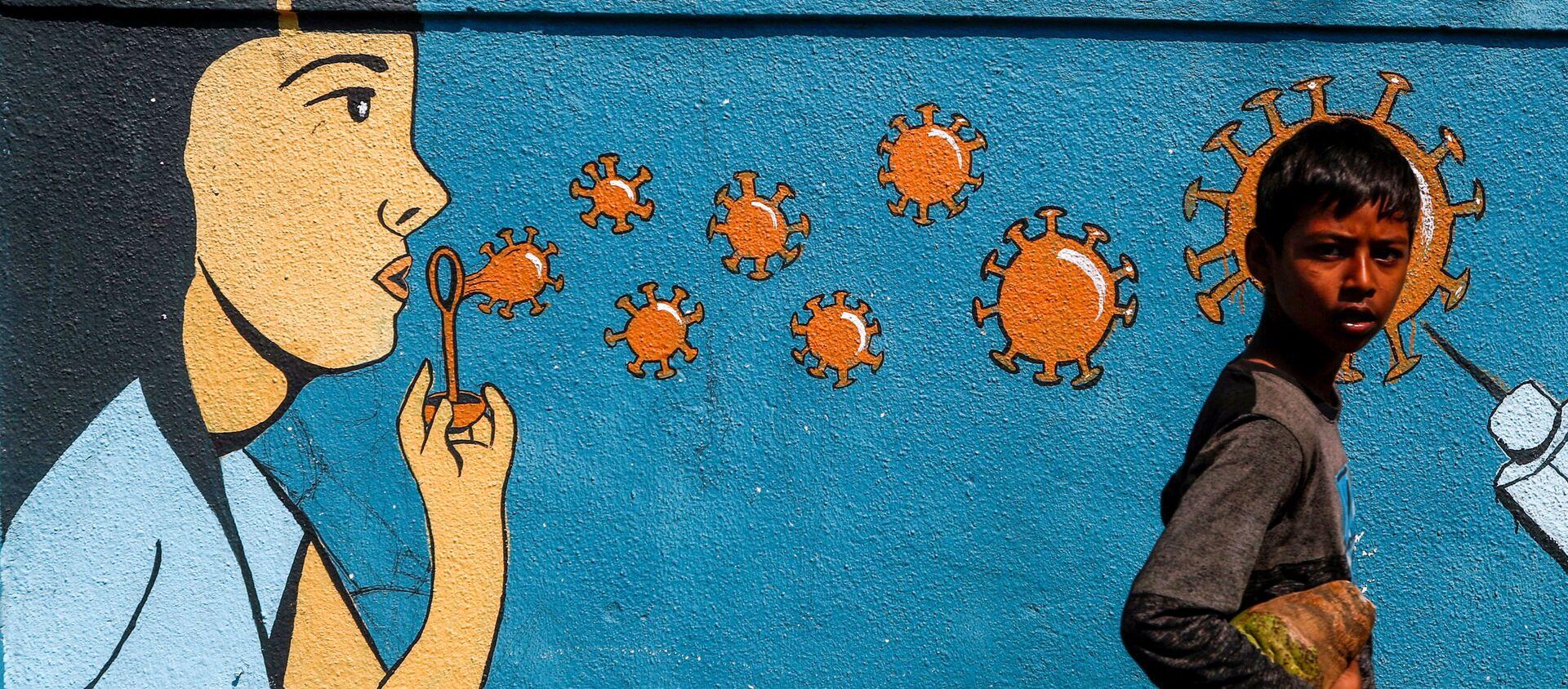 Chłopiec przechodzi obok graffiti w Bombaju w Indiach - Sputnik Polska, 1920, 01.05.2021