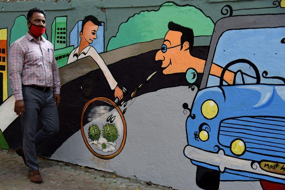 Pieszy przechodzi obok ściany z graffiti o tematyce koronawirusa w Bombaju w Indiach