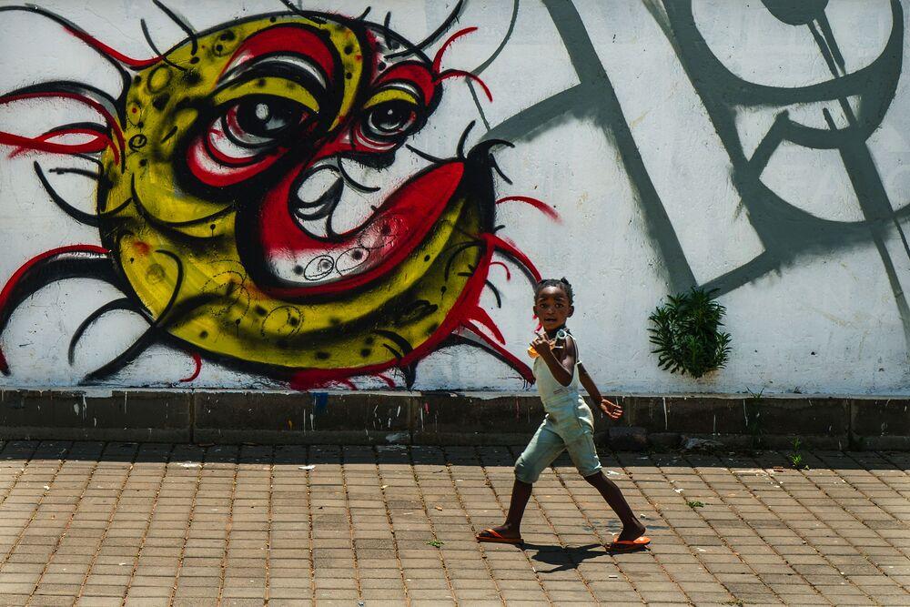 Dziecko z graffiti przedstawiającym COVID-19 w Soweto w RPA