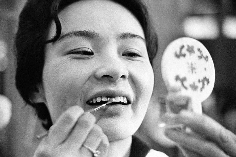 Japońska kobieta maluje zęby na czarno. Kiedyś to było oznaką urody