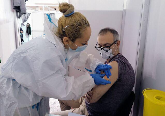 Mężczyzna zostaje zaszczepiony rosyjską szczepionką przeciw COVID-19 Sputnik V w Belgradzie