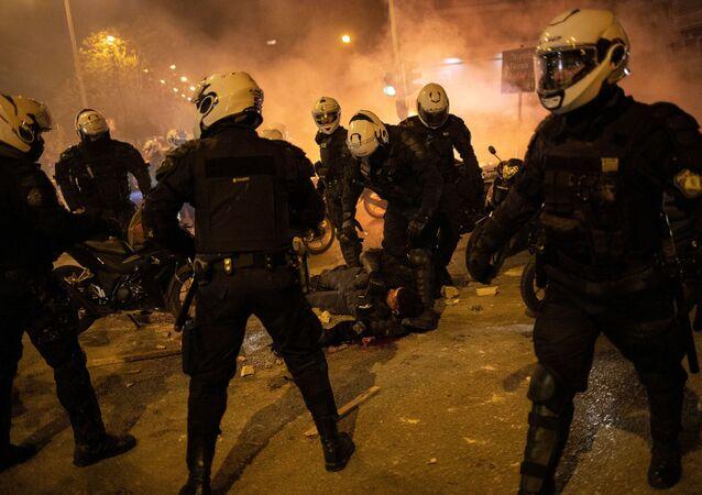 Policjanci stoją przy rannym w czasie demonstracji przeciwko brutalności policji w Atenach, Grecja
