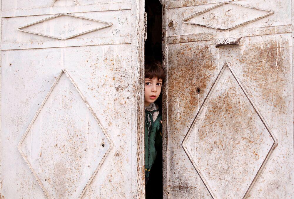 Dziecko wygląda z drzwi domu w Dumie, przedmieścia Damaszku, Syria
