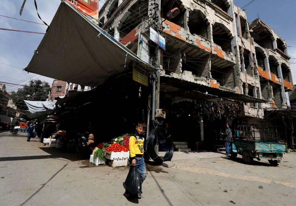 Chłopiec z reklamówką przed sklepem w syryjskim mieście Duma