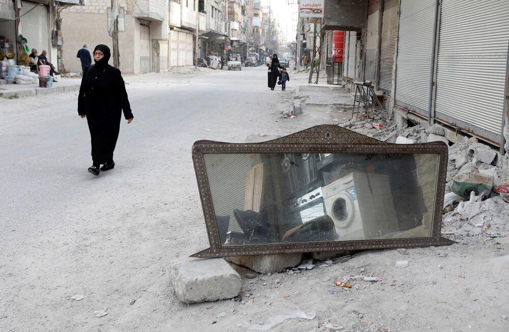 Kobieta przechodzi obok lustra na ulicy w syryjskim mieście Duma