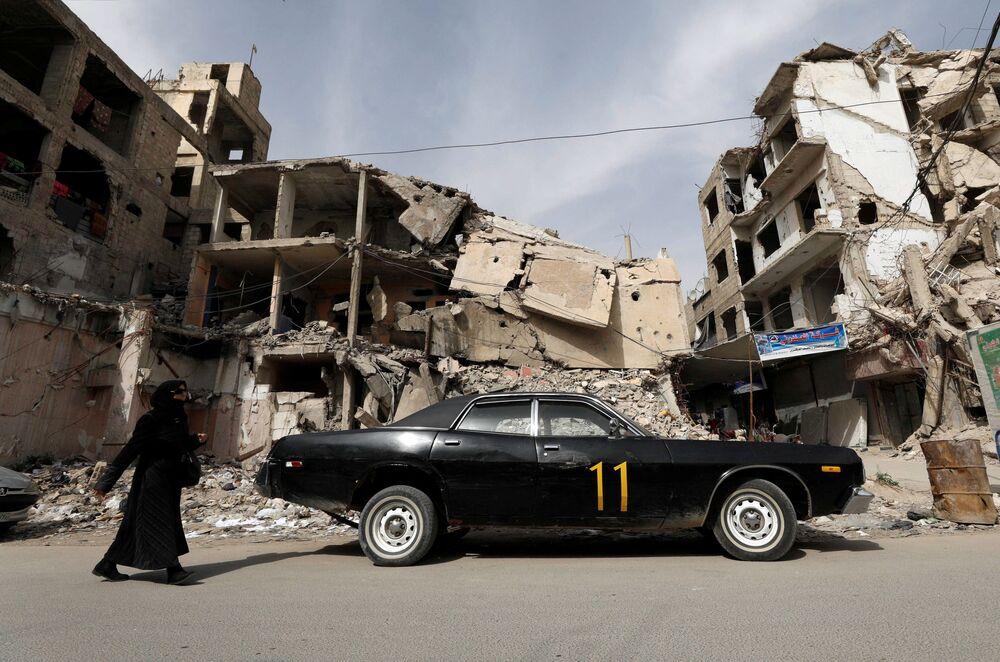 Kobieta przechodzi obok zniszczonego domu w Dumie, na przedmieściach Damaszku, Syria