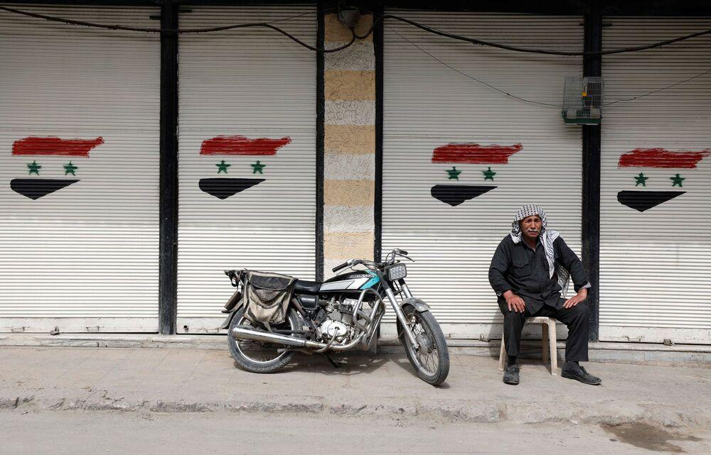 Mężczyzna siedzi przed zamkniętym sklepem w Dumie, na przedmieściach Damaszku, Syria