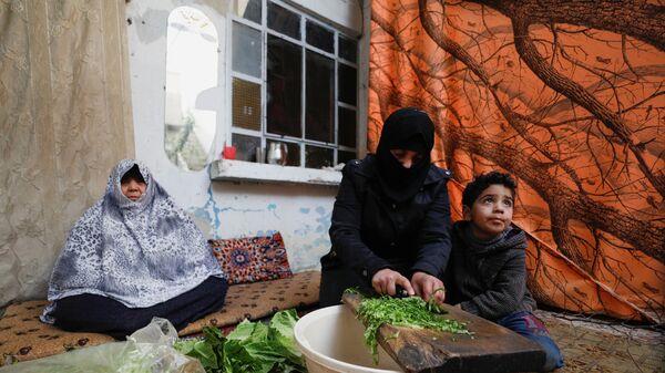 Syryjska kobieta gotuje jedzenie dla rodziny w Dumie, na przedmieściach Damaszku, Syria - Sputnik Polska