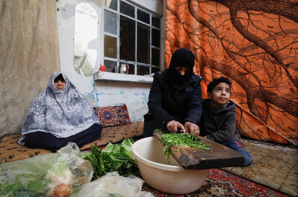 Syryjska kobieta gotuje jedzenie dla rodziny w Dumie, na przedmieściach Damaszku, Syria