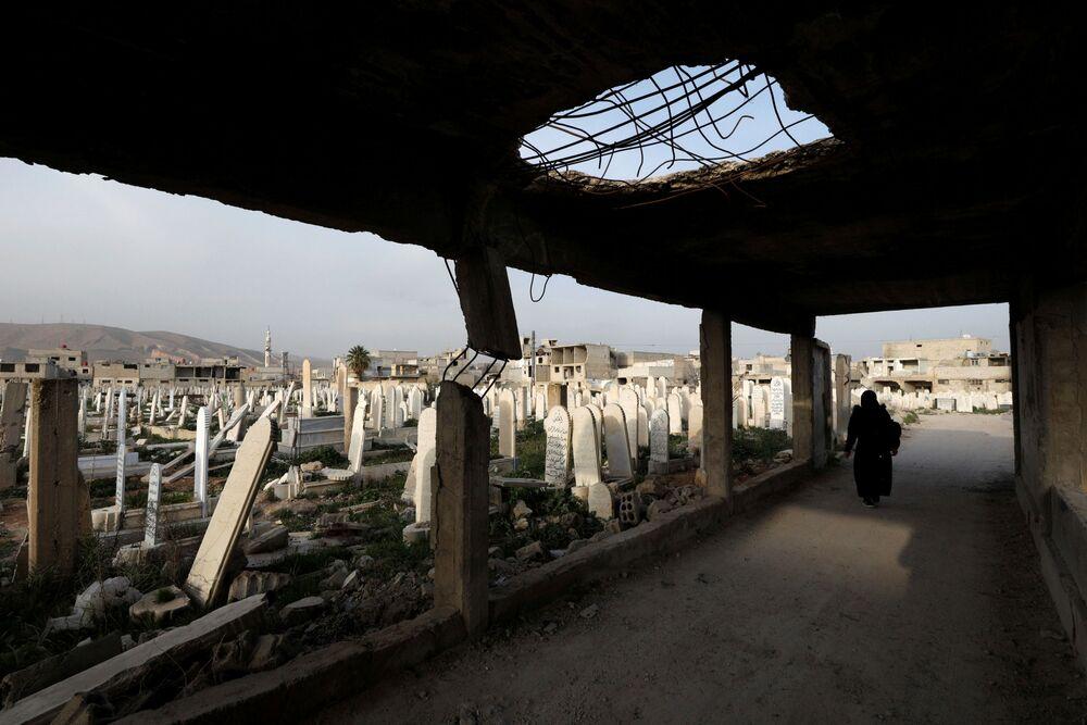 Kobieta idzie na cmentarzu w Dumie, na przedmieściach Damaszku, Syria