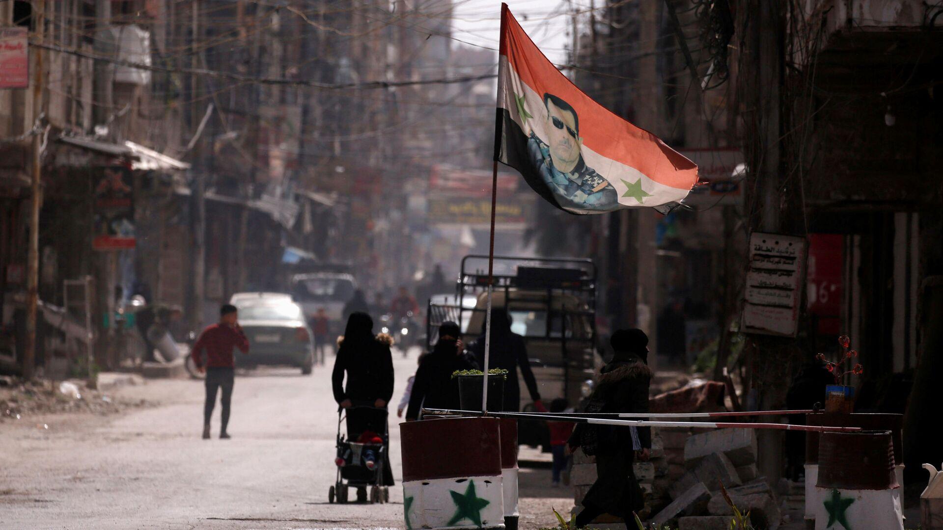 Flaga narodowa z wizerunkiem prezydenta Baszara al-Asada rozwiewa w punkcie kontrolnym w Dumie, na przedmieściach Damaszku, Syria - Sputnik Polska, 1920, 10.07.2021