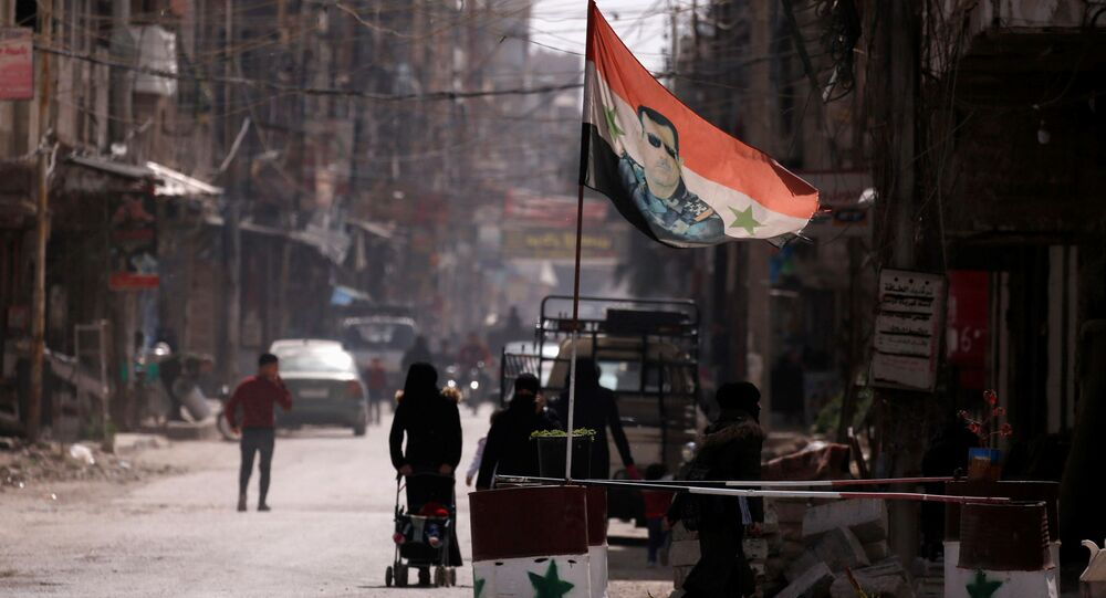 Flaga narodowa z wizerunkiem prezydenta Baszara al-Asada rozwiewa w punkcie kontrolnym w Dumie, na przedmieściach Damaszku, Syria
