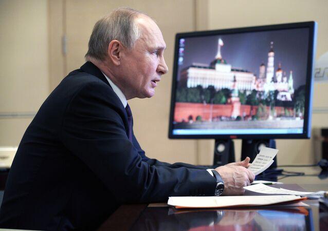 Władimir Putin, a w tle fotografia Kremla