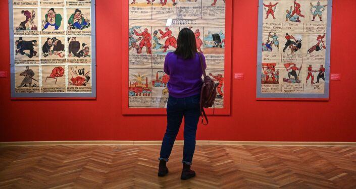 """Zwiedzająca ogląda plakaty """"Okna ROSTA"""" na wystawie """"Wojna polsko-radziecka1919-1921. Traktat ryski"""" w sali wystawowej Archiwum Federalnego w Moskwie"""