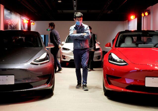 Sedan Tesla Model 3 i SUV Tesla Model X w salonie Tesli w Szanghaju.