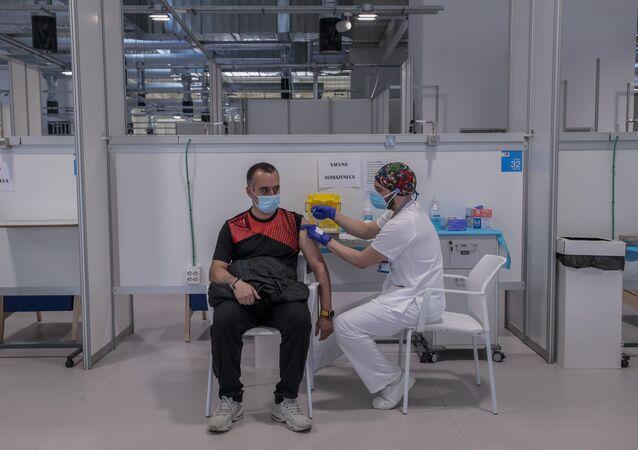 Mężczyzna otrzymuje szczepionkę AstraZeneca w szpitalu w Madrycie