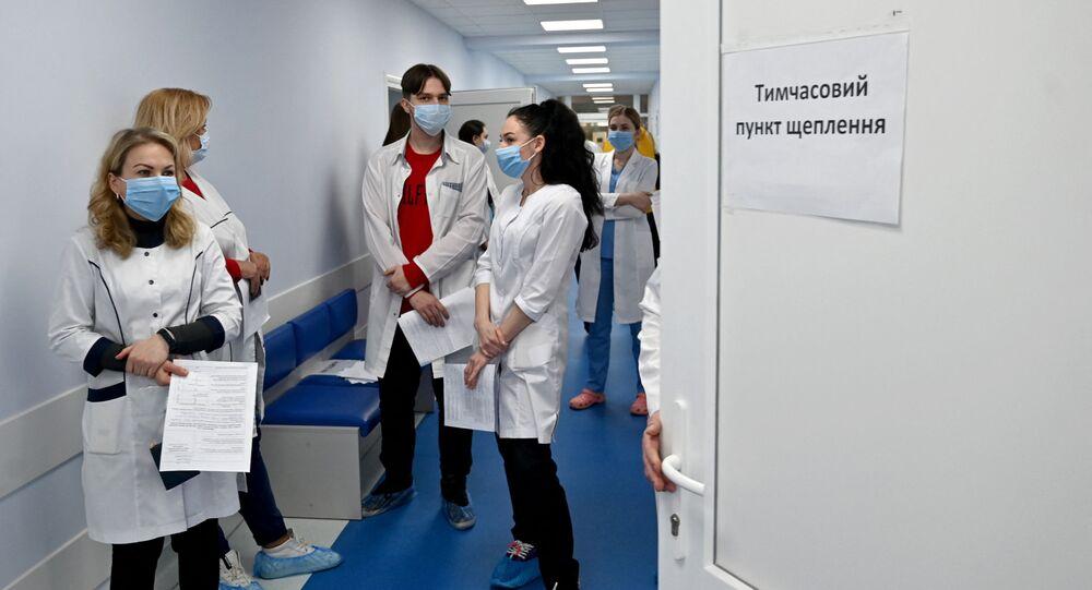 Pracownicy medyczni w kolejce po szczepionkę Oxford/AstraZeneca w szpitalu w Kijowie