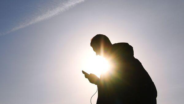 Mężczyzna ze smartfonem na jednej z ulic Moskwy - Sputnik Polska