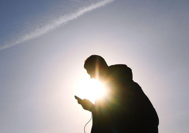 Mężczyzna ze smartfonem na jednej z ulic Moskwy