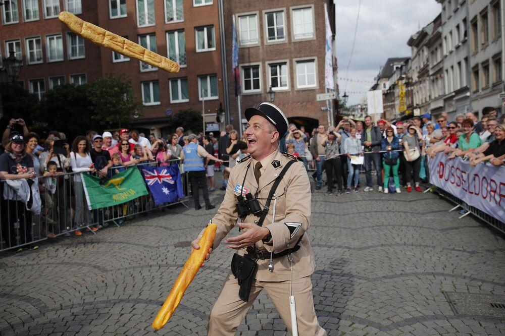 Mężczyzna przebrany za francuskiego żandarma z lat sześćdziesiątych żongluje dwiema bagietkami w Dusseldorfie w Niemczech