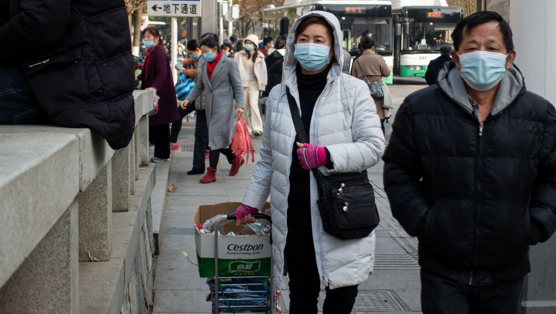 Ludzie w maskach ochronnych na ulicy w Wuhan w Chinach - Sputnik Polska, 1920, 29.05.2021