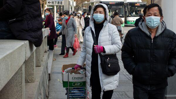 Ludzie w maskach ochronnych na ulicy w Wuhan w Chinach - Sputnik Polska