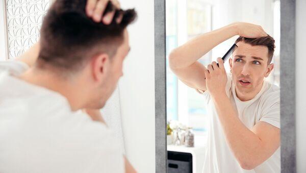 Mężczyzna ogląda swoje włosy w lustrze - Sputnik Polska