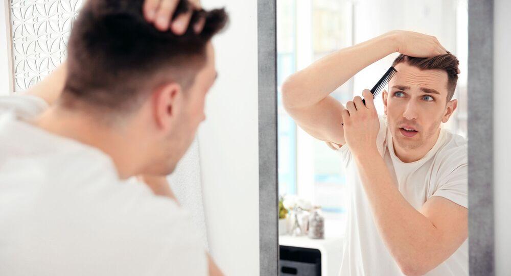 Mężczyzna ogląda swoje włosy w lustrze