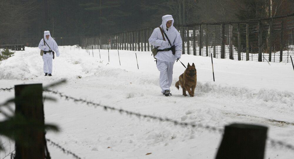 Białoruscy żołnierze z psem spacerują wzdłuż ogrodzenia z drutu na granicy z Polską