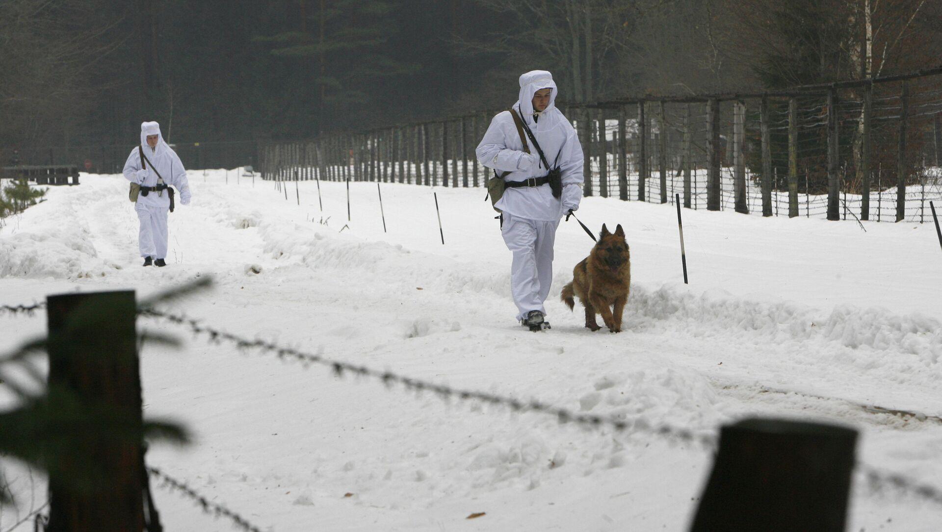 Białoruscy żołnierze z psem spacerują wzdłuż ogrodzenia z drutu na granicy z Polską - Sputnik Polska, 1920, 02.04.2021