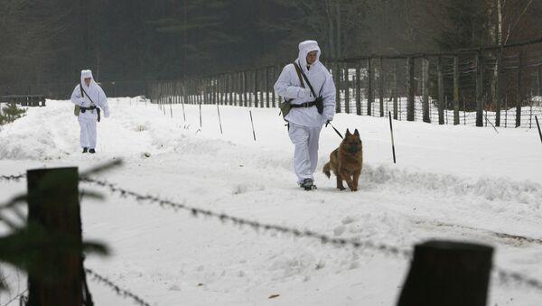 Białoruscy żołnierze z psem spacerują wzdłuż ogrodzenia z drutu na granicy z Polską - Sputnik Polska